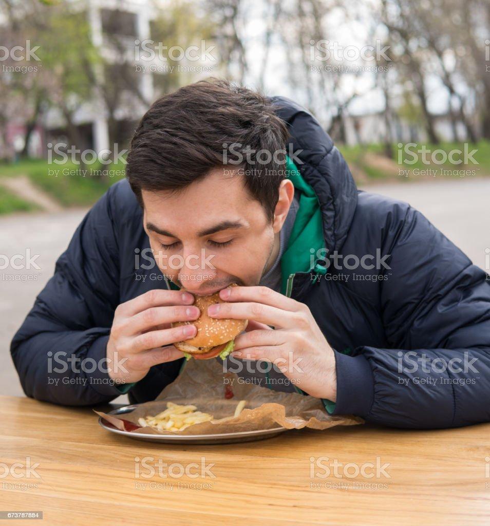 adam sokak gıda kafede çok lezzetli hamburger yeme royalty-free stock photo