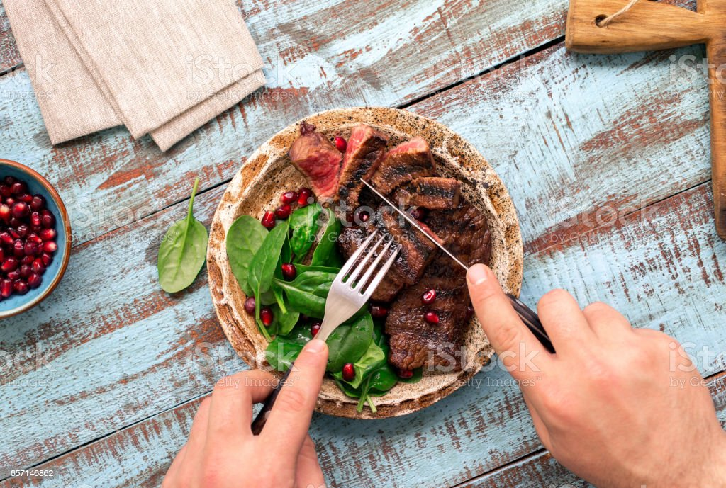 Man eats a beef grilled steak on wooden table. Rustic style stock photo