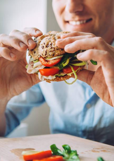 man isst eine große sandwich mit fleisch- und wegetables - gemüselaibchen stock-fotos und bilder