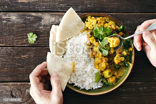 Man eats cauliflower spicy curry with rice and naan bread top view