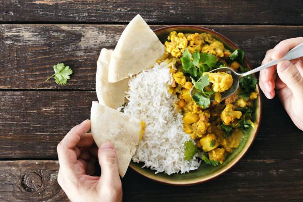 man eats cauliflower spicy curry with rice and naan bread - kapustowate zdjęcia i obrazy z banku zdjęć
