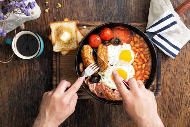 englisches frühstück isst der mensch - gefüllte eier stock-fotos und bilder