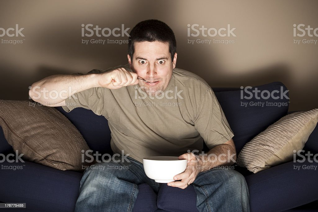 Man eats ice-cream fascinated by the TV stock photo
