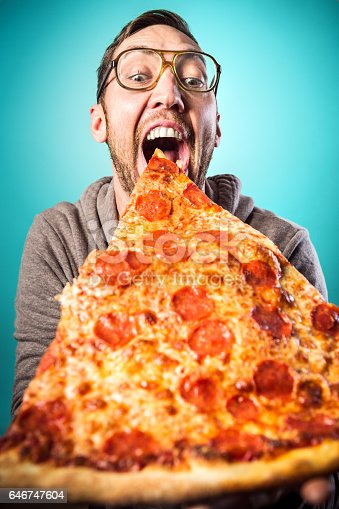 An adult man prepares to take a bite from a humorously large slice of pepperoni pizza, a look of joy and excitement on his face.  Vertical image with cyan / blue background.