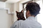 窓の横に猫を抱きしめる男