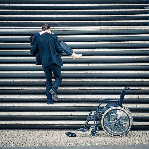 Man embracing his disabled woman walking up on the stairs stock photo