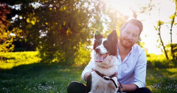man embracing his dog - dog and owner stock photos and pictures