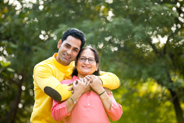Man embracing mother at park Happy man embracing his mother with love at park old mother son asian stock pictures, royalty-free photos & images