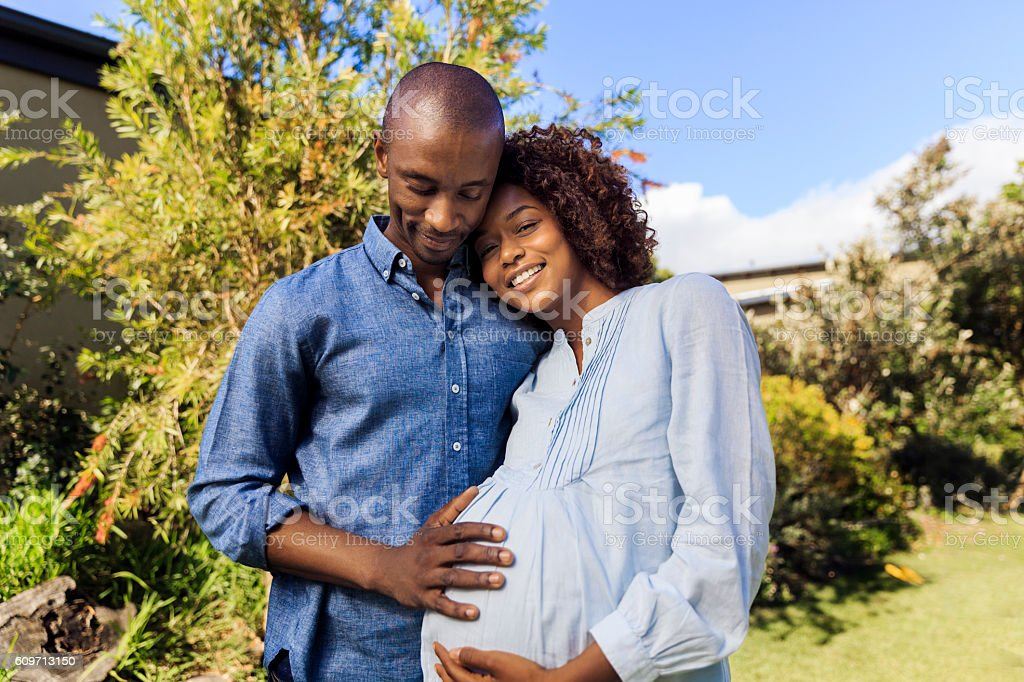 Man embracing pregnant woman in yard stock photo