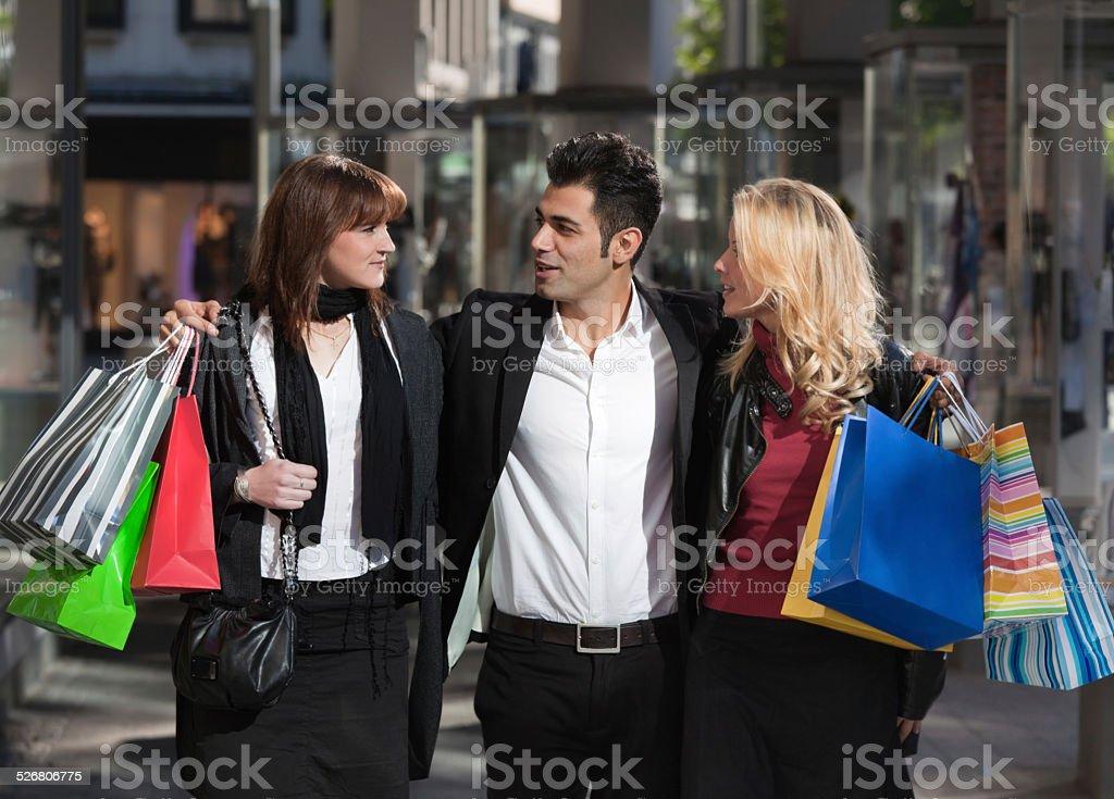 Man embracing two women walking with shopping bags stock photo