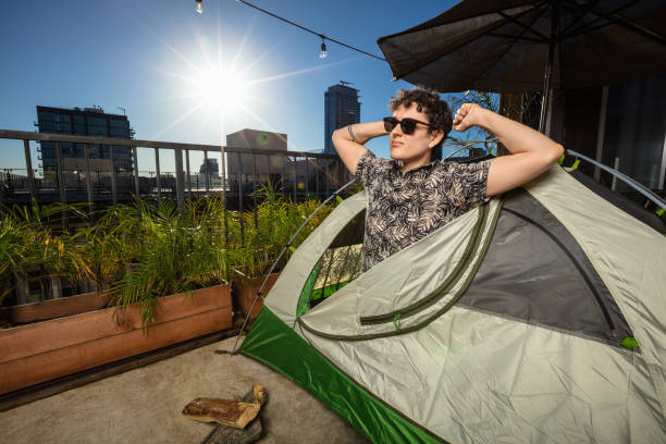 Man Emerging from Tent on Downtown Balcony