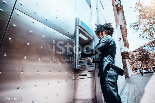 istock Man employer using outdoor automated teller machine 1076115754