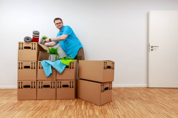 Man empties moving boxes stock photo