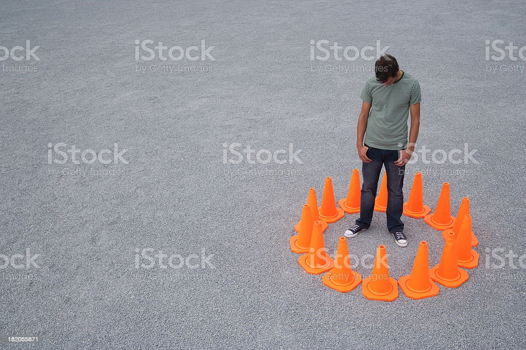 Man encircled by safety cones stock photo