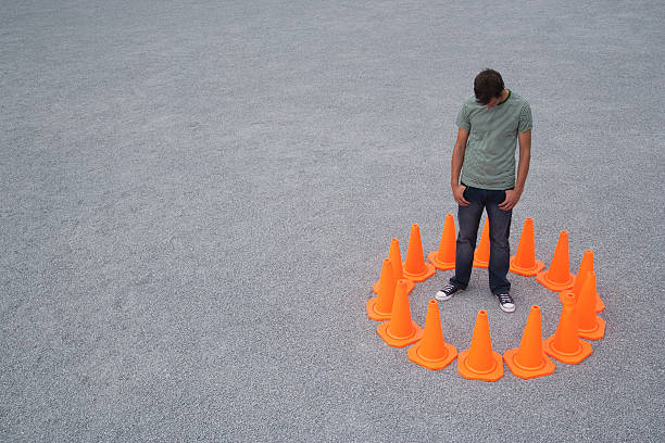 Man encircled by safety cones  trap stock pictures, royalty-free photos & images
