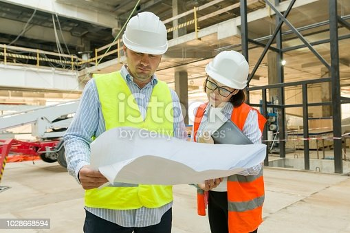 1129095769 istock photo Man engineer and woman architect at a construction site. Building, development, teamwork and people concept 1028668594