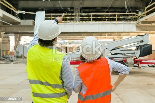 1129095769 istock photo Man engineer and woman architect at a construction site. Building, development, teamwork and people concept 1028669102