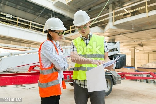 1129095769 istock photo Man engineer and woman architect at a construction site. Building, development, teamwork and people concept 1051151630