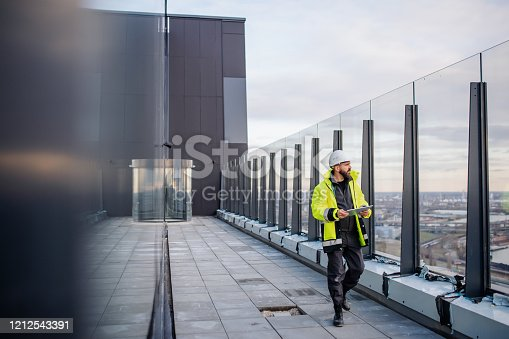994878714 istock photo Man engineer walking on construction site, holding tablet. 1212543391