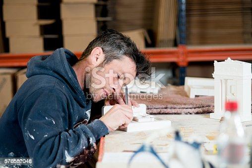 istock Man Engraving A Plaster Model Building 576582048