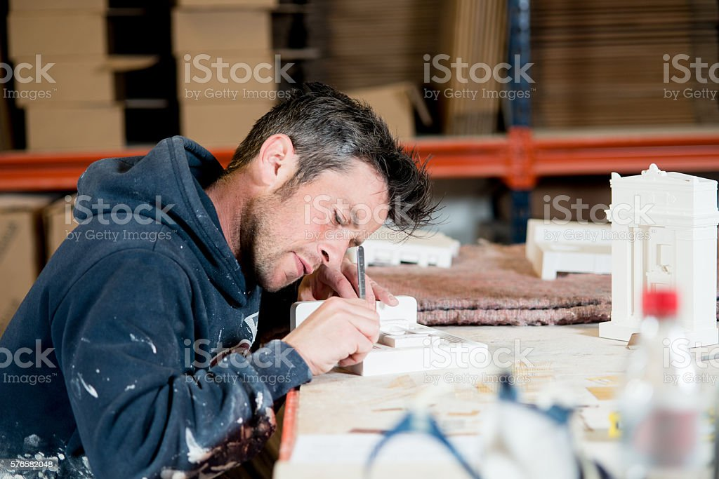 Man Engraving A Plaster Model Building stock photo