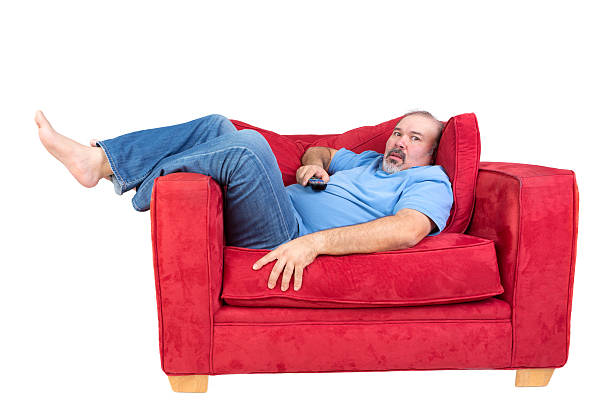 Man engrossed in watching television Man engrossed in watching television lying barefoot on a red couch with the remote control in his hand and a look of fascinated concentration, isolated on white sunken stock pictures, royalty-free photos & images