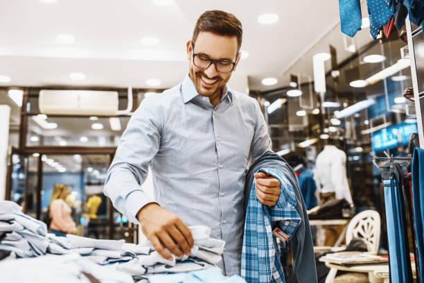 hombre enjoyig de compras - vestimenta fotografías e imágenes de stock