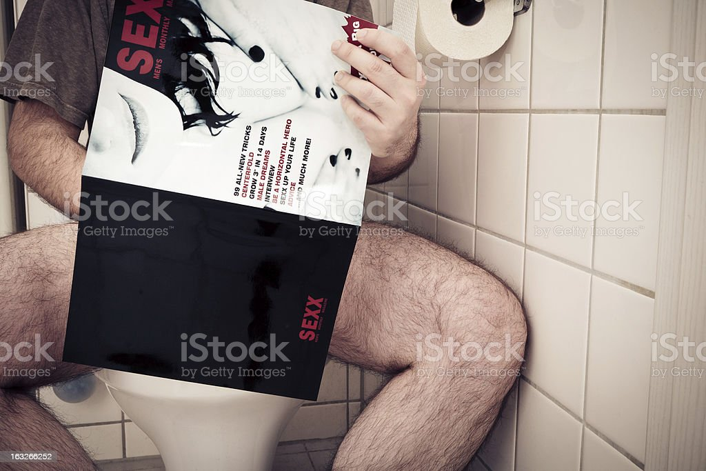 man enjoying a porn magazine royalty-free stock photo
