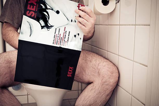 man enjoying a porn magazine stock photo