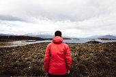 Happy man in red jacket staying on the small island at the Beagle Channel and looking at Andes mountains and Pacific Ocean, Argentina