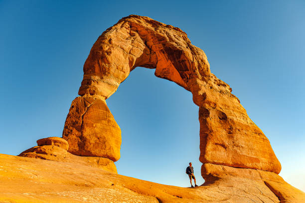 Man Enjoying Delicate Arch in Utah ,USA Man Enjoying Delicate Arch in Utah ,USA,Nikon D3x delicate arch stock pictures, royalty-free photos & images