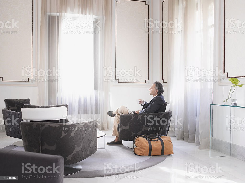 Man enjoying espresso in modern hotel suite stock photo