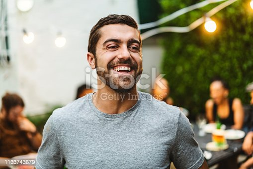 Happy young man enjoying garden party with friends in background. Cheerful bearded male is looking away. They are at backyard.