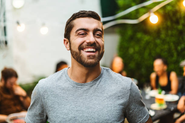 Man enjoying garden party with friends in yard stock photo