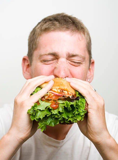 Man enjoying hamburger stock photo