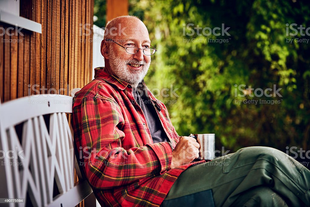 Man enjoying his garden with a cup of coffee stock photo