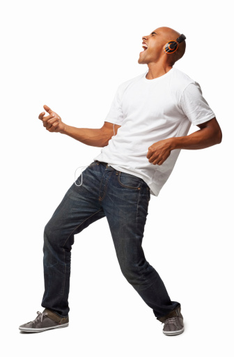 Full length of an ecstatic African American man playing air guitar while listening music on headphones. Vertical shot. Isolated on white.
