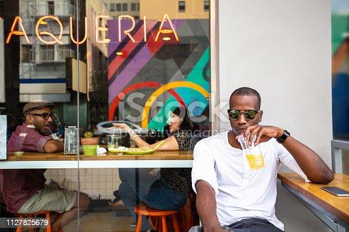 A Black man sitting outside a taqueria, drinking orange agua fresca.