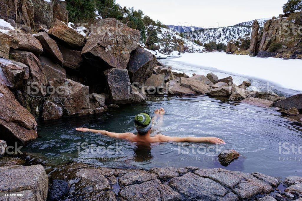 Man Enjoying Relaxing Soak in Natural Hot Springs in Winter Along the Colorado River stock photo