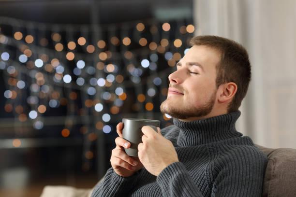 l'homme jouissant de sentir une tasse de café à la maison - tasse flat photos et images de collection