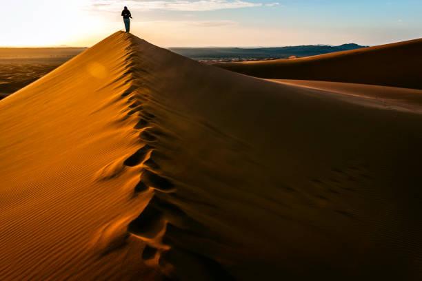 Man Enjoying Sunrise at Erg Chebbi Sand Dunes, Morocco, North Africa stock photo