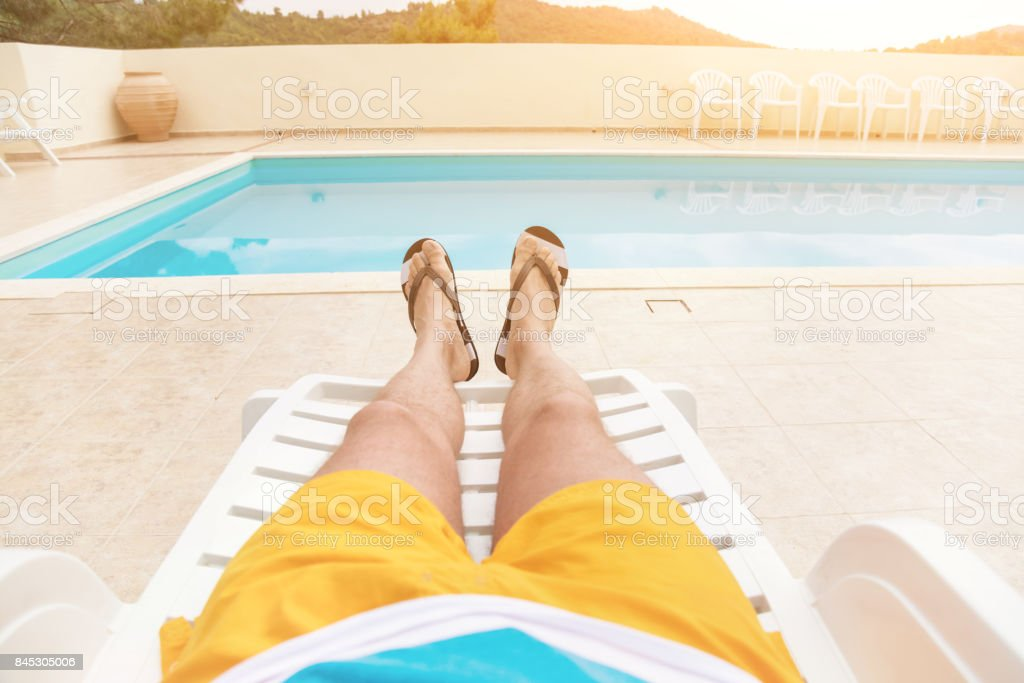 Man enjoying the summer by the pool. stock photo