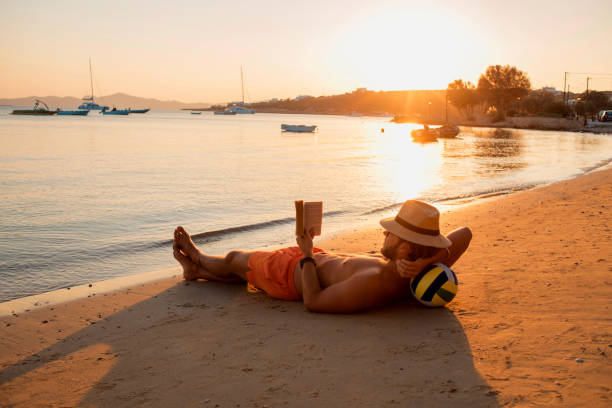 man enjoying the sunset on the beach stock photo