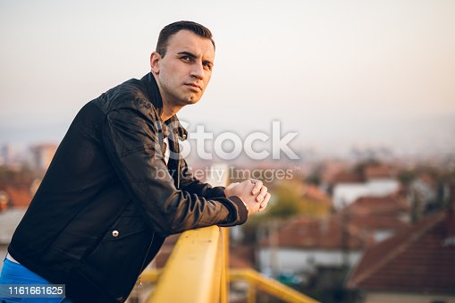 Man enjoying the sunset. Looking at the view. Wearing leather jacket and white t-shirt.