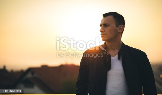 Man enjoying the sunset. Looking at the view. Wearing leather jacket and white t-shirt. Dramatic sky.