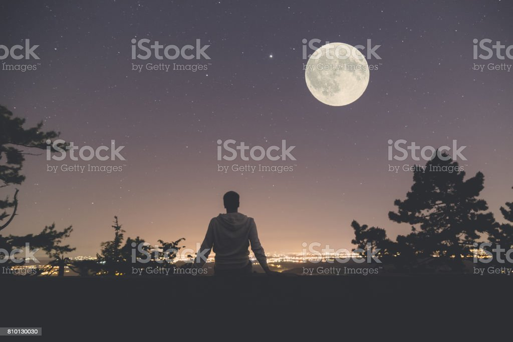 Man enjoying the view from hill above city. Full moon and stars on the sky. stock photo