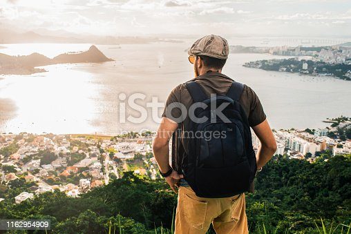 young man relaxing after a long hike to the top of the mountain