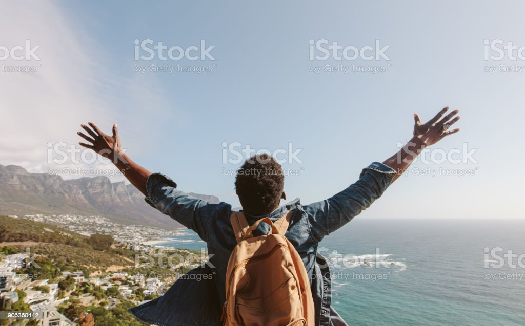 Man enjoying the view from top of mountain stock photo