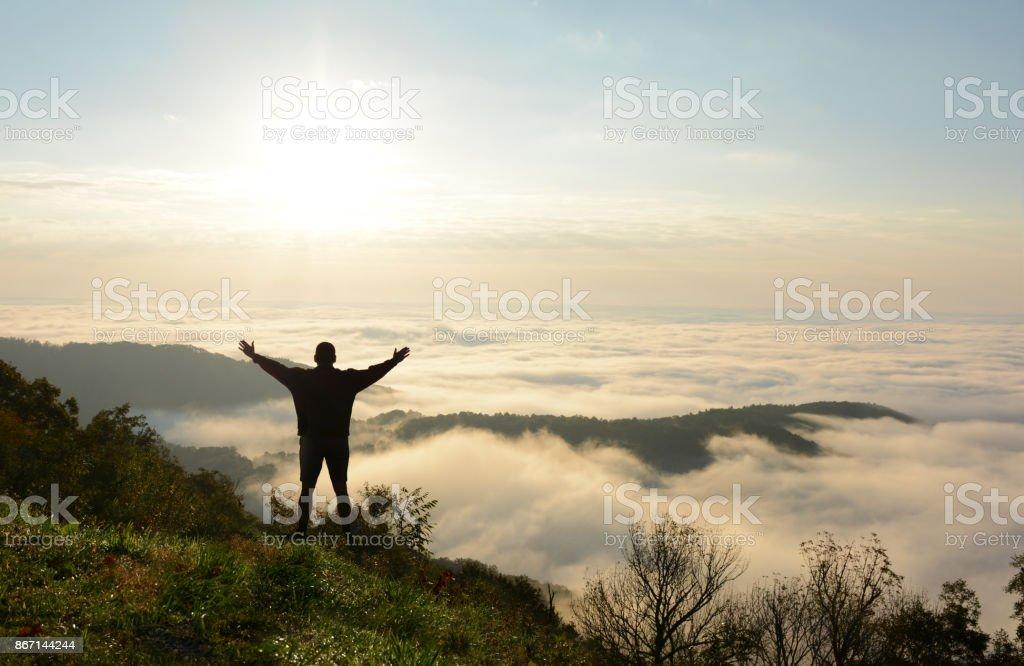 Man enjoying time on hiking trip on top of mountain. stock photo