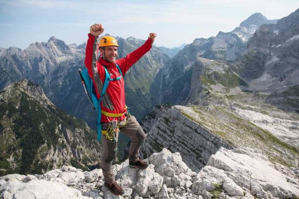 Mann genießt den Gipfel des Berges – Foto